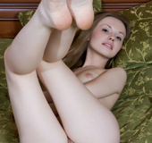 Dazzling young petite seductress nude on bed showing young ass and juicy