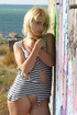 Blonde cutie takes off her striped tor vest to pose outdoors