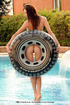 Enticing naked lady poses with an inner tube at the pool.