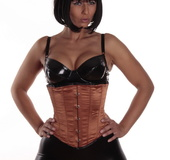 Girl with golden skin and a bob haircut in a sexy corset and tight, shiny