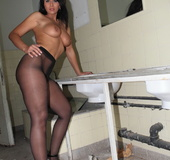 In an industrial washroom, slut inserts a glass dick into her pierced