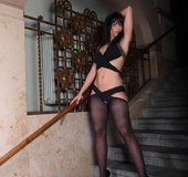 Brunette on fancy staircase wearing crotchless black hosiery and black