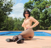 Brunette stunner lounging poolside in black toe-to-waist nylons and sexy