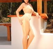 Brunette wearing sunglasses and full spaghetti-strap nude nylon bodysuit