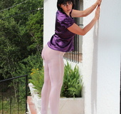 Lady unbuttons purple satin top and reaches into white nylons to pay attention
