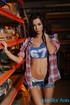 Mischievous brunette doll in a checked shirt and jeans shorts prefers