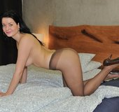 Black-haired honey in heels and nylons spreads her long legs wide open