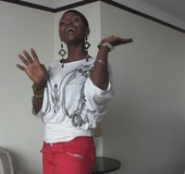 Alluring African chick takes off her white blouse with gray design and