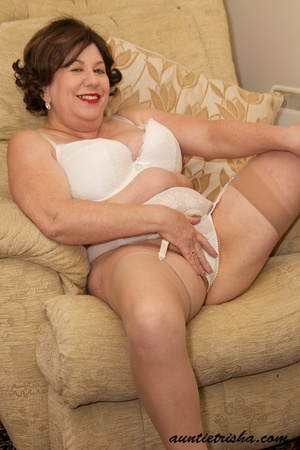 Old babe with golden brown hair wearing black dress with white and green floral designs takes it off then rubs her pussy on a brown couch wearing her white lingerie, brown stockings and black high heels before she takes off her bra and release her huge juggs. - XXXonXXX - Pic 11