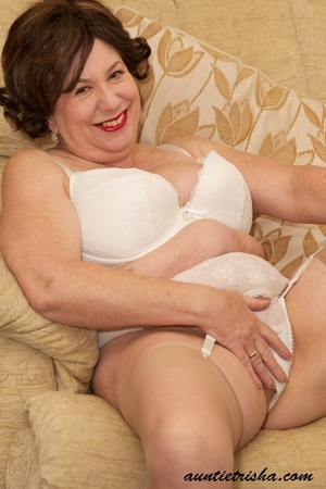Old babe with golden brown hair wearing black dress with white and green floral designs takes it off then rubs her pussy on a brown couch wearing her white lingerie, brown stockings and black high heels before she takes off her bra and release her huge juggs. - XXXonXXX - Pic 12