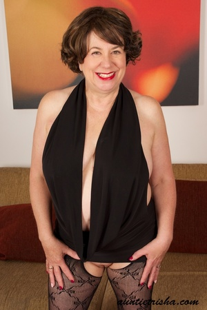 Mature brunette shows her old cleavage and pussy in her elegant black dress, stockings and high heels then exposes her huge breasts on a brown couch. - XXXonXXX - Pic 2