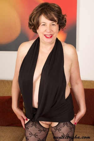 Mature brunette shows her old cleavage and pussy in her elegant black dress, stockings and high heels then exposes her huge breasts on a brown couch. - XXXonXXX - Pic 5