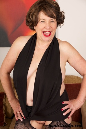 Mature brunette shows her old cleavage and pussy in her elegant black dress, stockings and high heels then exposes her huge breasts on a brown couch. - XXXonXXX - Pic 6