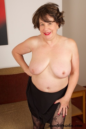 Mature brunette shows her old cleavage and pussy in her elegant black dress, stockings and high heels then exposes her huge breasts on a brown couch. - XXXonXXX - Pic 14