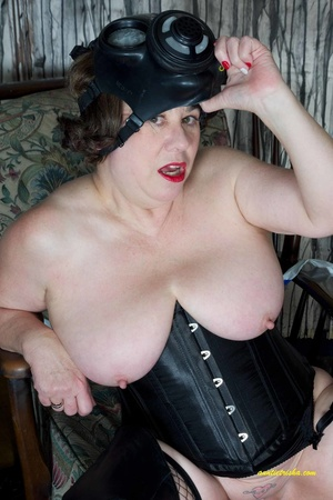 Hot old chick with a gas mask bares her huge breasts in black corset, fishnet stocking and boots before she sits on a silver steps and reveals pussy. - XXXonXXX - Pic 7