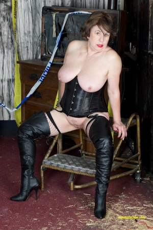 Hot old chick with a gas mask bares her huge breasts in black corset, fishnet stocking and boots before she sits on a silver steps and reveals pussy. - XXXonXXX - Pic 11