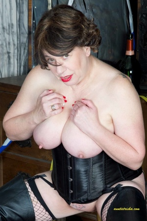 Hot old chick with a gas mask bares her huge breasts in black corset, fishnet stocking and boots before she sits on a silver steps and reveals pussy. - XXXonXXX - Pic 13