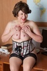 Mature secretary takes off her pink and white stripe polo and black skirt