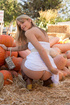 Mischievous blonde freshie in a white dress in seductive poses outdoors