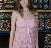 Angelic fledgling in a pink nightie gets naked in front of the fireplace.