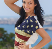 Captivating vamp in a stars and stripes shirt and bikini posing by the