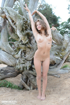 Pretty babe displays her sexy curves while she slowly strips off her blue dress and pose her stunning body in white bikini before she takes off her bra and shows her tiny boobs then strips down her panty and shows her indulging pussy by a big tree at the beach. - XXXonXXX - Pic 18