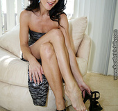 MILF hottie shows her sexy legs as she sits on a white couch wearing her