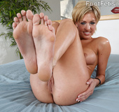 Lusty blonde in black gets feet licked, works cock with sexy feet and