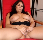 Busty Asian brunette in black top and short skirt plays with tits and