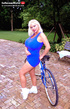 Dazzling blonde in blue top and short skirt rides bicycle then plays with