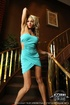 Luscious blonde darling in red shoes posing on the staircase