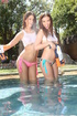 Two fine brunettes having fun with water pistols in the pool