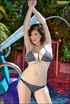 Dark haired girl in sexy bikini works on her tan by the pool