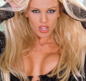 Blond bombshell with big breasts in black-lace bra and panties rubs her
