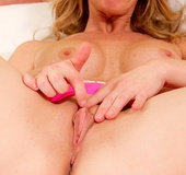 Playful blonde MILF with pink underwear fingers her bare pussy.