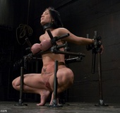 MILF's great tits are placed in a large rack compactor during her heated