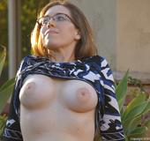 Curvy brunette gal pours water on her titties in public