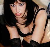 Mistress in a black lingerie and red lipstick teases and touches herself