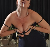 Horny mature redhead in blue dress plays seductively with cigarette smoke