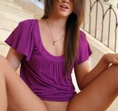 Cute brunette in a purple blouse teases her wet pussy with her pink toy