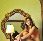 Brunette in orange pantie set shows off and fingers plump pink pussy
