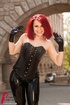 Banging redhead in black leather corset, pants and boobs pose outdoor
