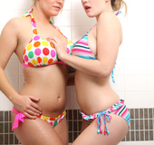 Two hot babes with giant boobs take a shower together.