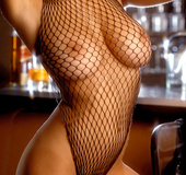 Busty brunette in black jacket and fishnet garter shows hairy cunt, tits