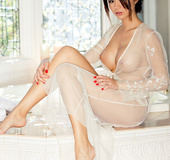 Tattooed cute brunette in white net outfit shows firm pointy tits in bedroom