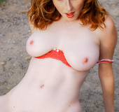 Curvy redhead in red bra and blue panties models tits and hairy pussy