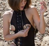 Kinky slut in bodysuit teases her hot clamped nipples in public.