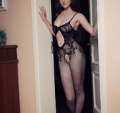 Stunning brunette dons kinky black lingerie, lies on rug to fondle pussy!