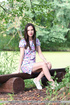 Brunette girl takes a hike in nature and gets naked on bench.