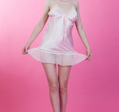 Slender chick takes off pink silk peignoir to show pussy